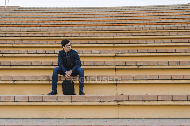 Young businessman with backpack sitting on stairs looking at distance — Stock Photo