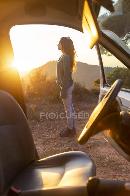 Young woman on a road trip, taking a break, looking at view — Stock Photo