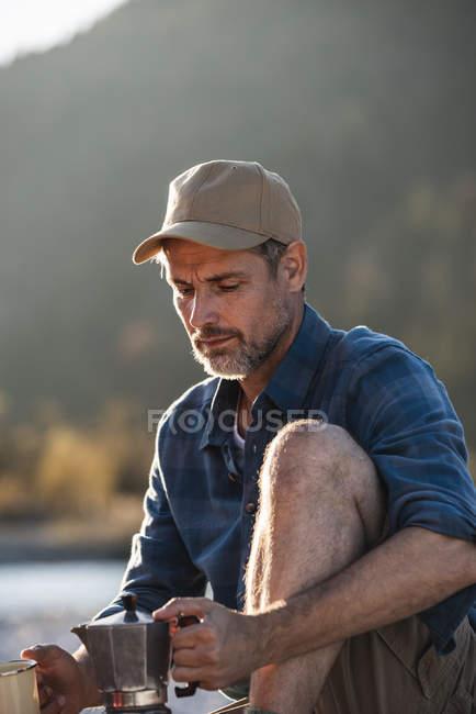 Mature man camping at riverside, using espresso machine — стоковое фото