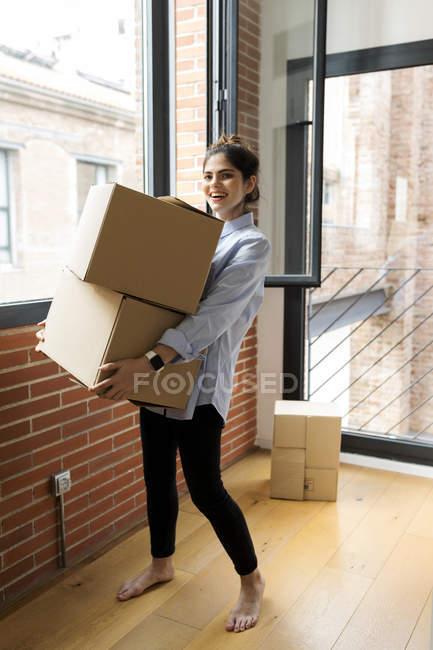 Retrato de joven sonriente llevando cajas de cartón en un nuevo apartamento en la ventana - foto de stock