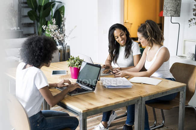 Three women with laptop and documents talking at table — Stock Photo