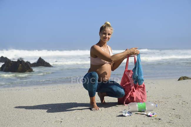 Femme enceinte nettoyant la plage des déchets plastiques — Photo de stock