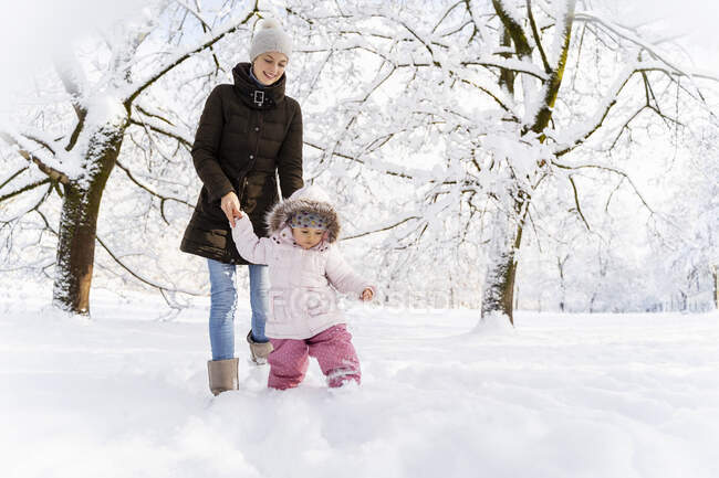 Счастливая мама гуляет с дочкой по зимнему пейзажу — стоковое фото