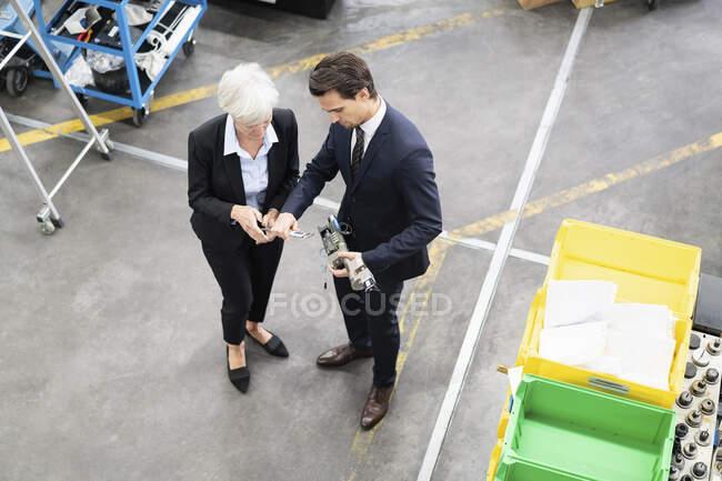 Бизнесмен и старшая бизнесвумен осматривают детали на фабрике — стоковое фото
