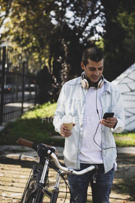 Молодой человек с велосипедом и кофе на вынос проверяет сотовый телефон — стоковое фото