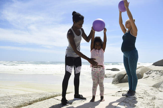 Mother with daughter and friend exercising with a ball on the beach — Stock Photo