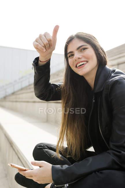 Щаслива молода жінка, сидячи на сходах з стільникового телефону і жестами — стокове фото