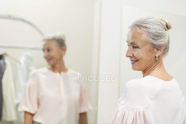 Улыбающаяся пожилая женщина в бутике, отраженная в зеркале — стоковое фото