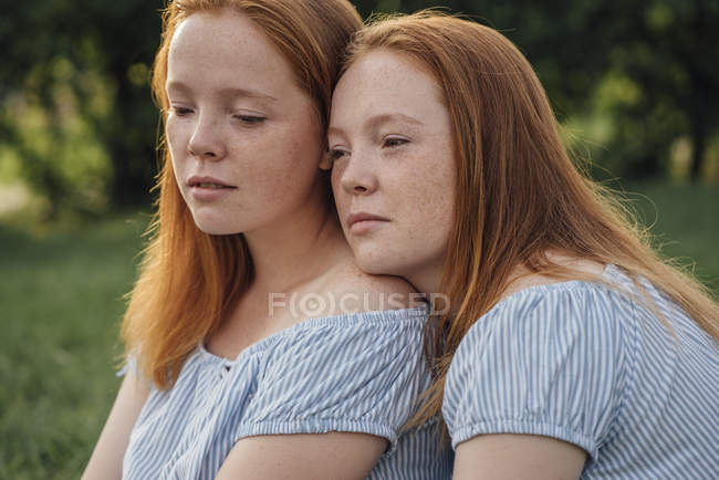 Redheaded twins hugging in park — Foto stock