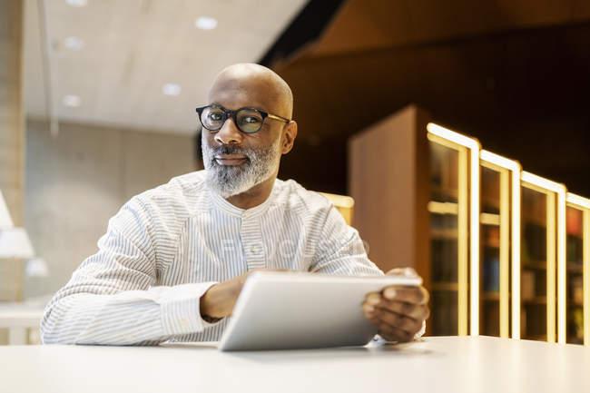 Retrato de homem maduro sentado na mesa em uma biblioteca com tablet digital — Fotografia de Stock