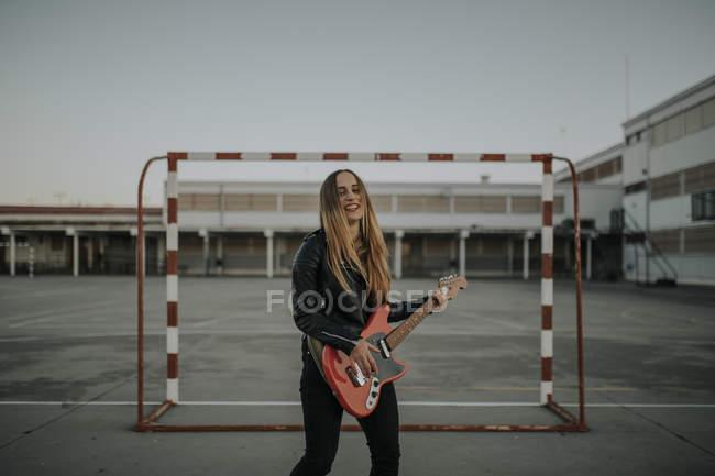 Ritratto di giovane donna felice che suona la chitarra sul campo sportivo — Foto stock