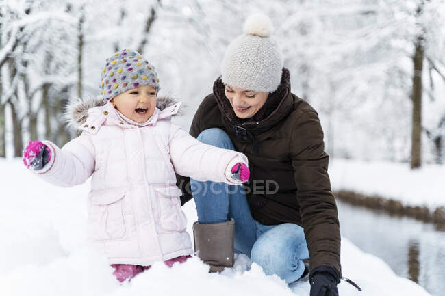 Happy mother with daughter in winter landscape — Stock Photo