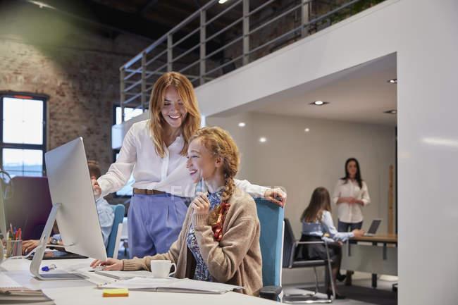 Молодая женщина, работающая в современном творческом офисе, коллега, дающая советы — стоковое фото