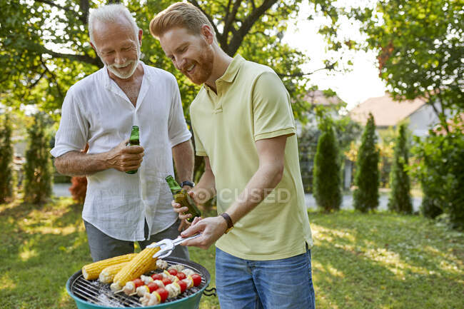 Senior father and adult son having a barbecue in garden — Stock Photo
