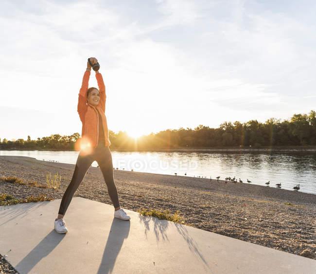 Молода жінка, яка здійснює з кеттбелл біля річки — стокове фото
