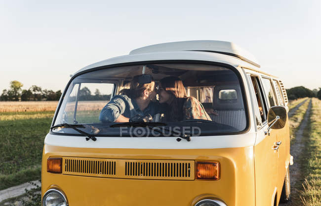Happy couple sitting in their camper, kissing — стоковое фото