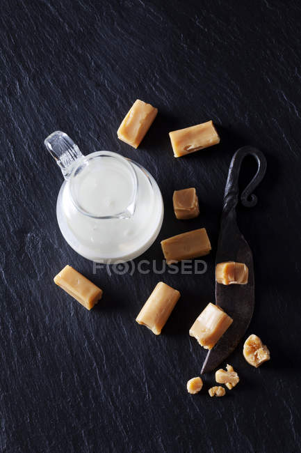 Fresh cream toffees and a carafe of cream — Stock Photo