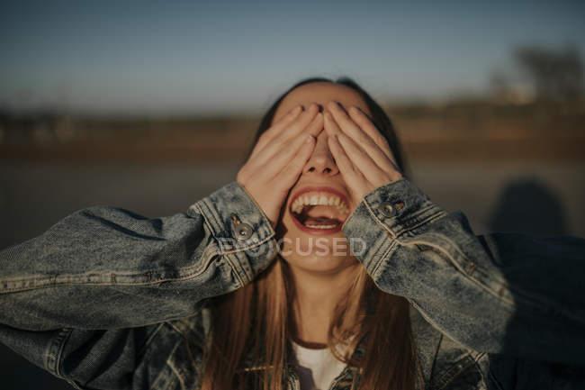 Joven alegre cubriendo sus ojos al aire libre - foto de stock