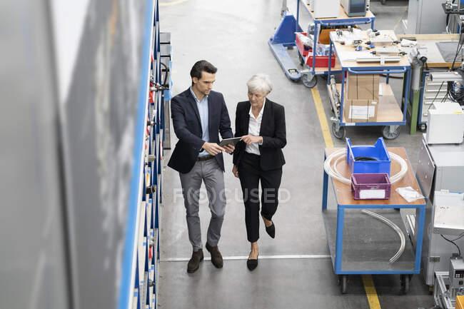 Imprenditore e imprenditrice senior con tablet a piedi in una fabbrica — Foto stock