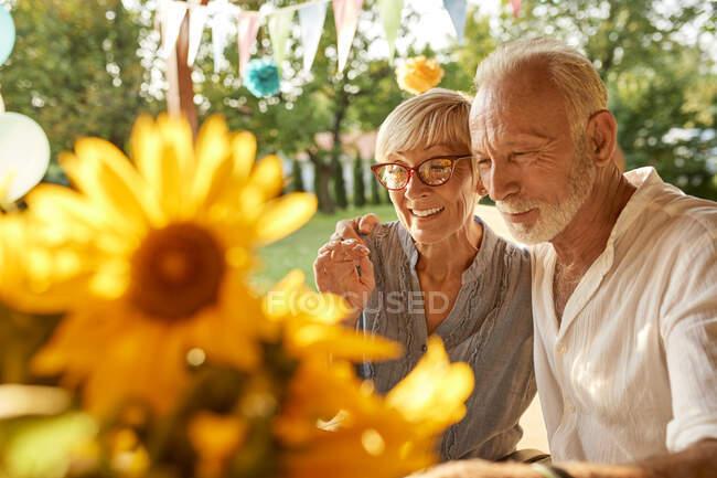 Glückliches Senioren-Paar umarmt sich auf Gartenparty — Stockfoto