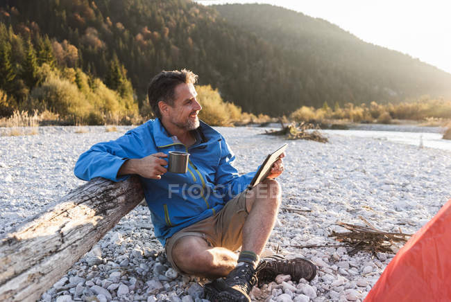 Mature man camping at riverside, using tablet — Stock Photo