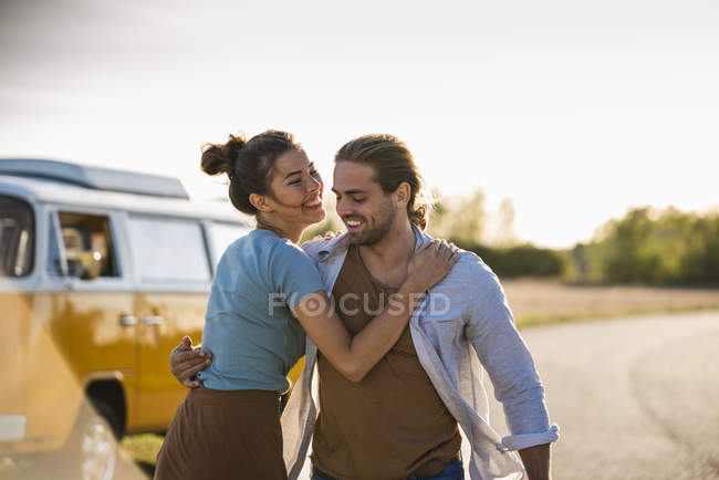 Happy couple doing a road trip with a camper, embracing on the road — Stock Photo