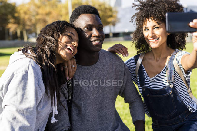 Трое друзей проводят время в городе, делают селфи со смартфоном — стоковое фото
