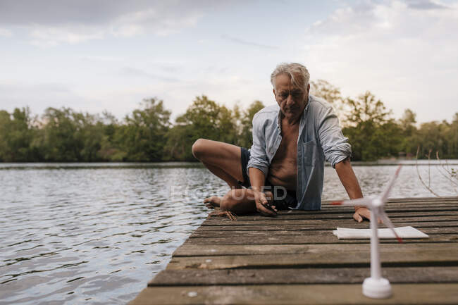Senior man sitting on jetty at a lake with small wind turbine model — Stock Photo