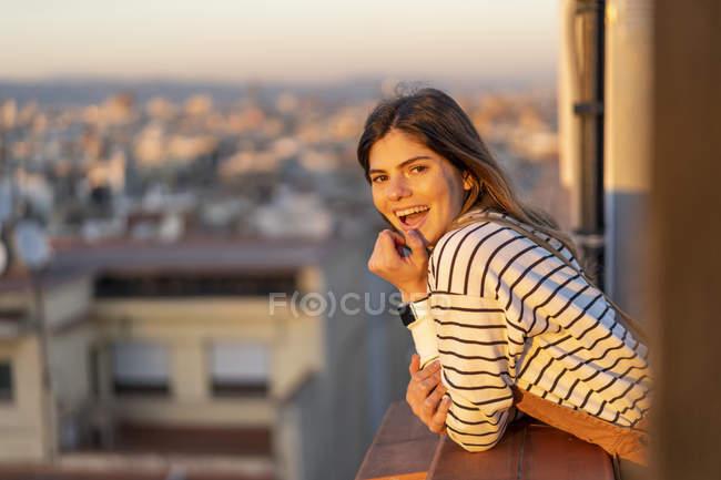 Portrait de jeune femme riante sur le balcon au coucher du soleil — Photo de stock
