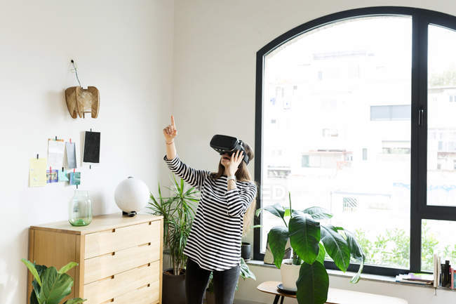 Young woman at home wearing VR glasses — Foto stock