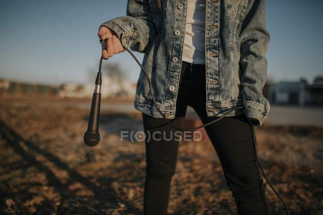 Закрытие глаза на молодую женщину, держащую микрофон на улице — стоковое фото