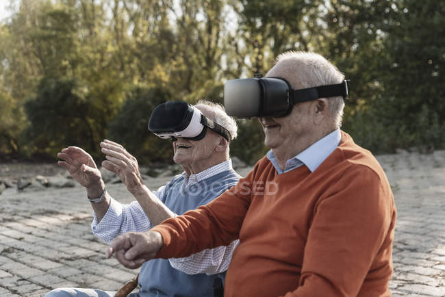 Two old friends sitting by the riverside, using VR glasses — Stock Photo