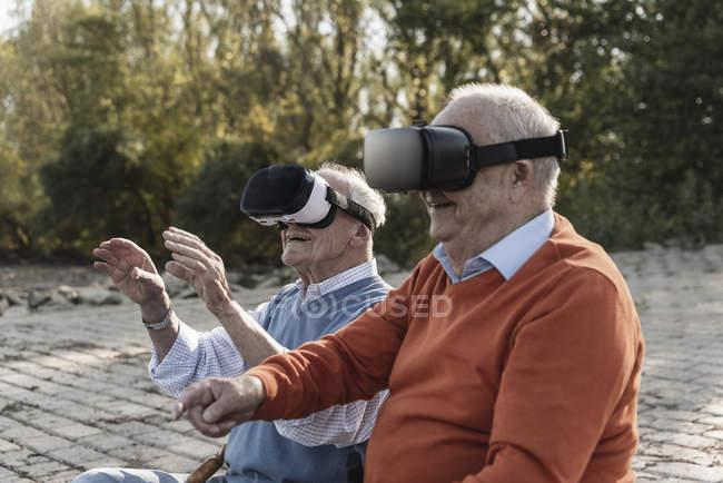 Два старых друга сидят у реки, используя очки от виртуальной реальности — стоковое фото
