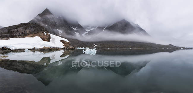 Greenland, Sermersooq, Kulusuk, Schweizerland Alps, mountains reflecting in water — Stock Photo