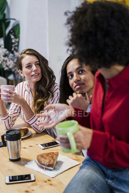 Trois femmes parlent à table — Photo de stock