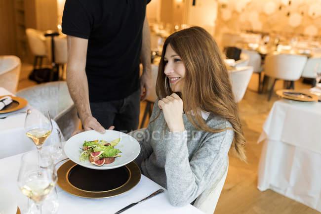 Офіціант служить блюдо для усміхнена жінка в ресторані — стокове фото
