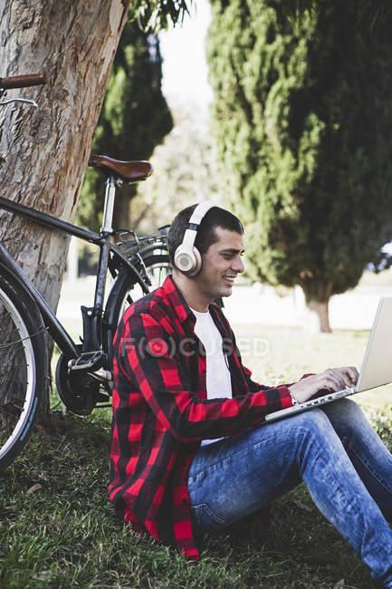 Junger Mann sitzt mit Kopfhörern im Park und benutzt Laptop neben Fahrrad — Stockfoto