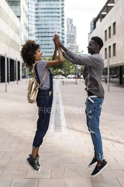 Coppia felice che salta e dà il cinque in strada — Foto stock