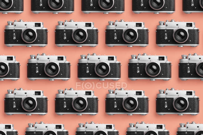Photo cameras organized in a row over coral color background — Stock Photo