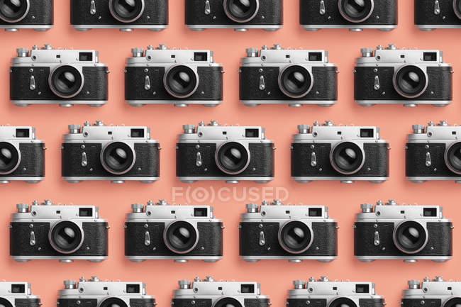 Fotocamere organizzate in fila sopra lo sfondo a colori corallo — Foto stock