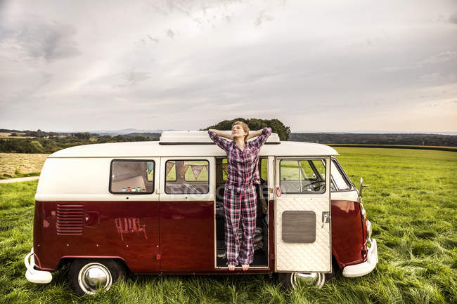 Woman in pyjama stretching in a van in rural landscape — Stock Photo