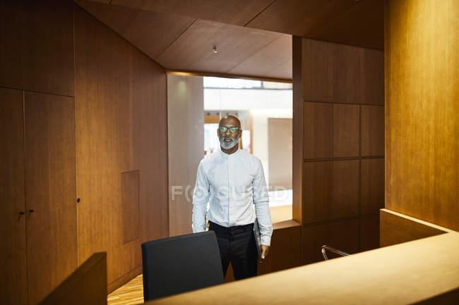 Портрет зрілого чоловіка з ноутбуком на робочому місці з дерев'яною панеллю. — стокове фото