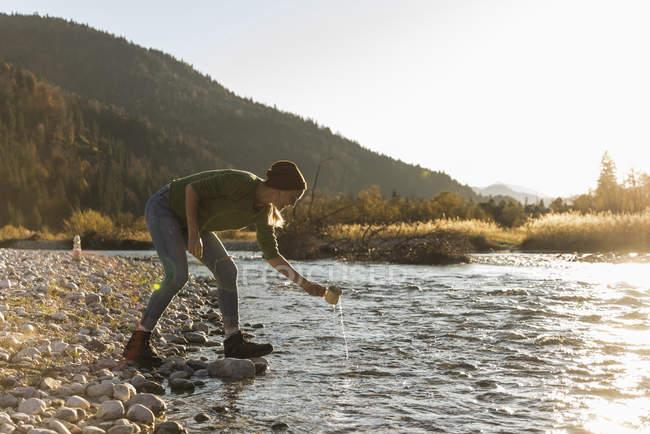 Mulher madura no beira-rio com caneca — Fotografia de Stock