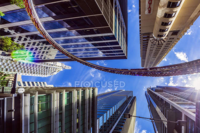 Australia, New South Wales, Sydney, High-rise buildings, low angle view against the sun — Stock Photo