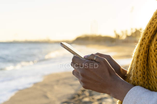 Woman with yellow scarf, using smartphone on the beach — Stock Photo
