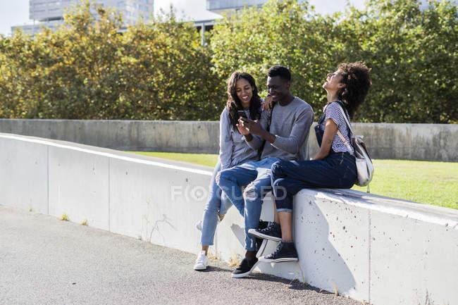 Трое друзей проводят время в городе, используя смартфон — стоковое фото