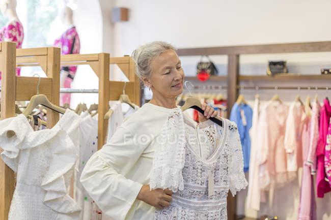 Улыбающаяся пожилая женщина покупает одежду в бутике — стоковое фото