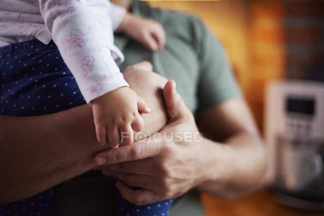 Крупный план отца, держащего малышку дома — стоковое фото