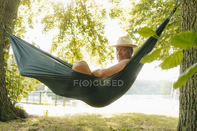 Senior man wearing straw hat relaxing in hammock at lakeshore — Stock Photo