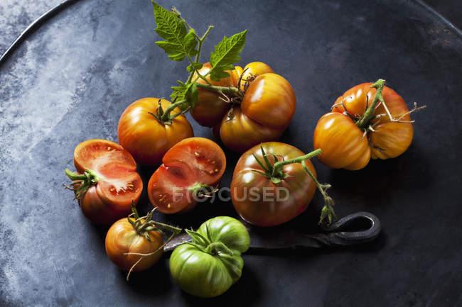 Tomates de ternera enteros y en rodajas 'Chocolate Stripes' y cuchillo en terreno oscuro - foto de stock